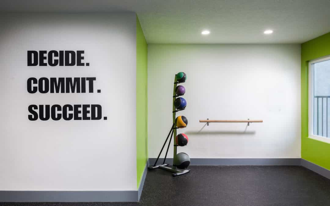 White wall Decide, Commit, Succeed together with ballet bar and medicine balls