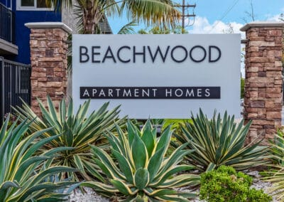 Beachwood Apartments front sign monument with green plants